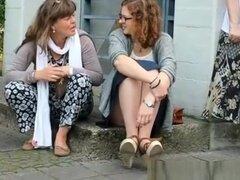 Mirar bajo la falda, mira bajo la falda de una chica que está sentada en el bordillo.