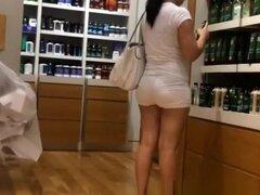 ¡Mujer de Latina de gran culo en shorts muy ajustados, mujer latina de gran culo en shorts muy ajustados blanco en una tienda de perfumes.