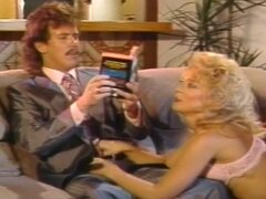 Nina Hartley Is An Aggressive Fuck Whore, Curly haired blond slut Nina Hartley is an aggressive minx who will take all the cock she can get. Stud Tom Byron is sitting on the sofa trying to read aloud to her from a book, but she completely ignores his words; instead she shamelessly gets down on her knees and starts to suck his cock! Tom is in seventh heaven as she unleashes her awesome oral skills on his pole, slobbering all over the shaft and making his pubic hair dripping wet with her saliva. Tom doesn't have to do a thing as Nina removes the rest of her clothes, revealing her bald pussy and extremely large breasts and lowering her slippery slit down on the pole.