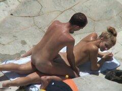 Rubia se la follan en la playa, esta hermosa rubia puta llegó a una playa nudista a pasar un buen rato con su novio. Los chicos le follan por detrás, mientras estaba haciendo este voyeur amateur video.