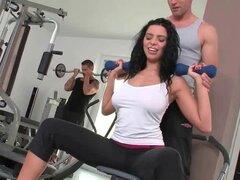 Chica deportiva tetona seduciendo a dos chicos en el gimnasio