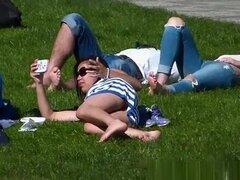 Mirar bajo la falda de una chica acostado en la hierba, mira bajo la falda de una chica que está descansando en la hierba en el parque.