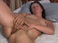 Peluda madura Carmen jugando su coño en la cama. Peluda madura Carmen jugando su coño en la cama