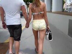 Chica en un sexy shorts para caminar alrededor de la ciudad, chica en una sexy shorts va a caminar con un amigo en la ciudad.