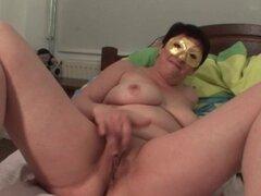 Enmascarado madura frotándose su coño afeitado. Madura nena desnuda vistiendo una máscara y masturbándose en la cama