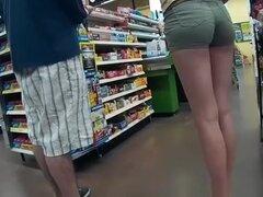En apretados pantalones cortos verdes, chica chica con buen culo en shorts muy ajustados verdes en el supermercado.