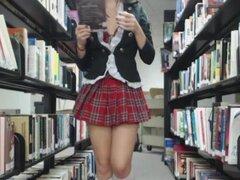 Colegiala en uniforme quiere busto su tuerca en la biblioteca