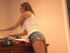 Chica en shorts de jeans hace una pedicura y camina alrededor de la casa