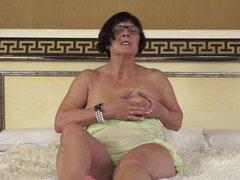 Abuela gorda con gafas golpea su bola de la piel con juguete