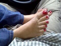Con el pie a través de pantalones en un coche con las uñas de rojo brillantes y sorprendentes pies